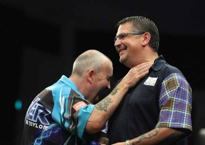 Gary Anderson and an opponent laughing during a match