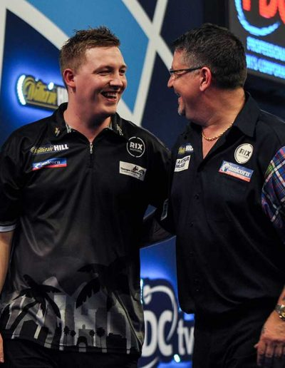 Gary Anderson and an opponent laughing during a darts match