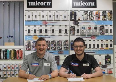 Adam Hunt & Chris Dobey in front of a unicorn darts display